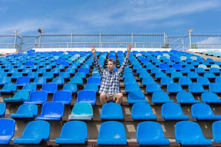 One fan in an empty sports stadium