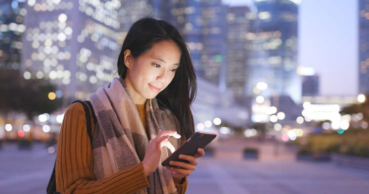 Smiling woman using smartphone on new cellphone plan