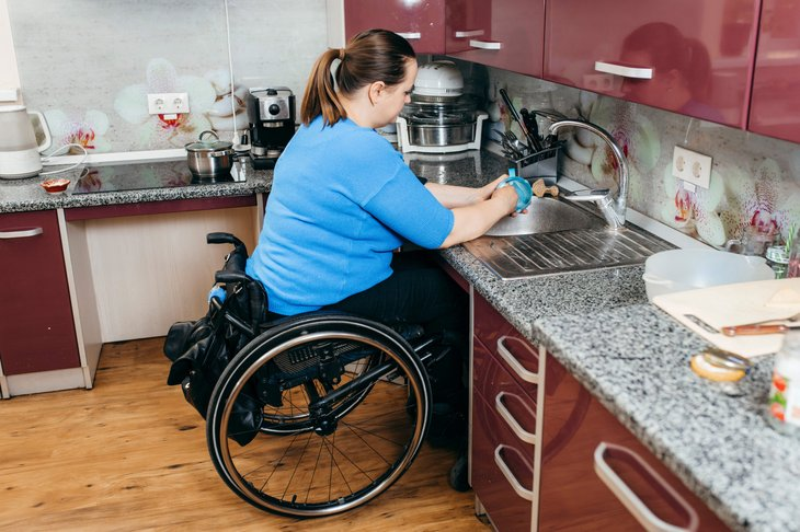 Woman in an accessible kitchen with low countertops