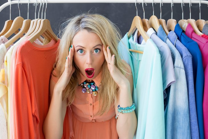Frustrated woman in clothes closet