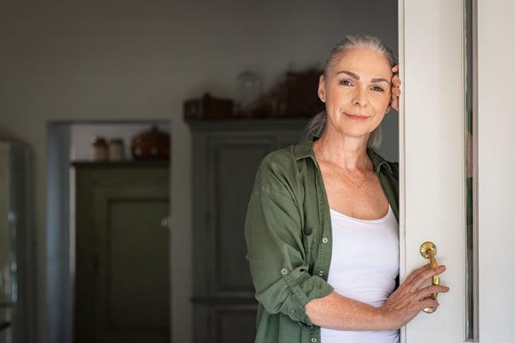 Older woman in a wide doorway of her home