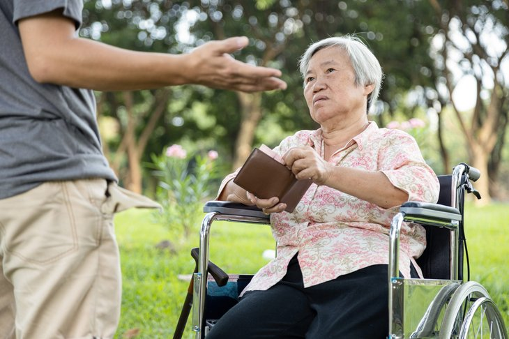 Woman in a wheelchair giving money to her adult child