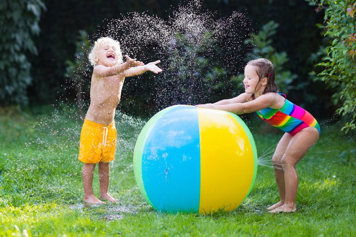Children playing in a sprinkler on a summer day