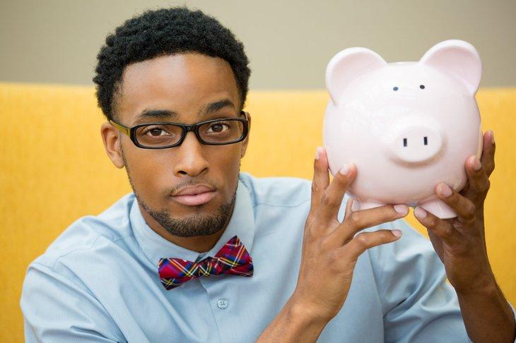 Smart man holding a piggy bank
