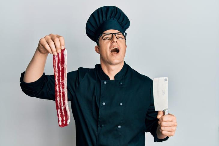 Unhappy man holding bacon