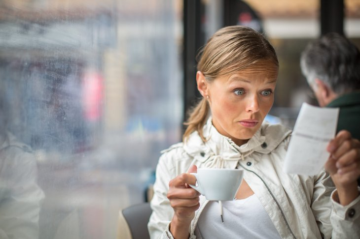 Woman looking at expensive restaurant bill