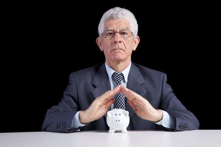 Senior businessman with piggy bank
