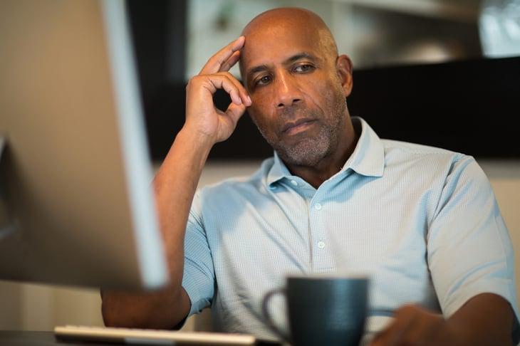 Man worrying at his computer desk