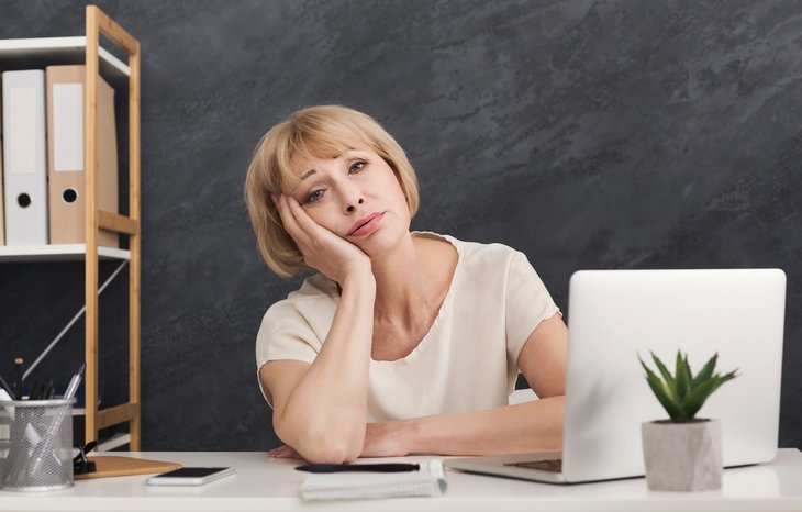 Unhappy middle-aged woman at work