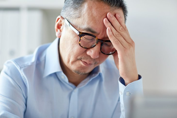 A stressed older worker holding his forehead