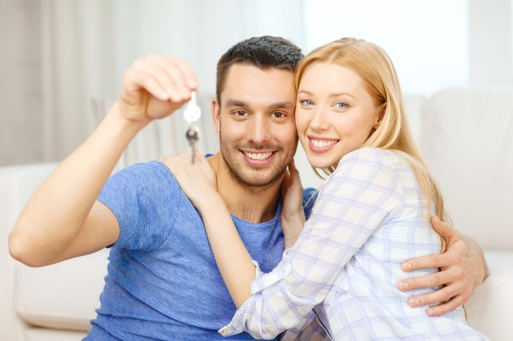 Couple holding keys at home