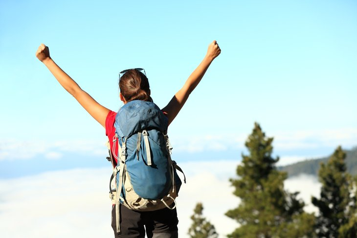 Backpacker with arms raised triumphantly