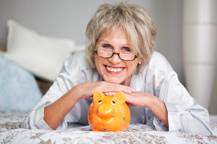 A senior woman in glasses smiles while he rests her hands on a piggy bank and lies on a bed