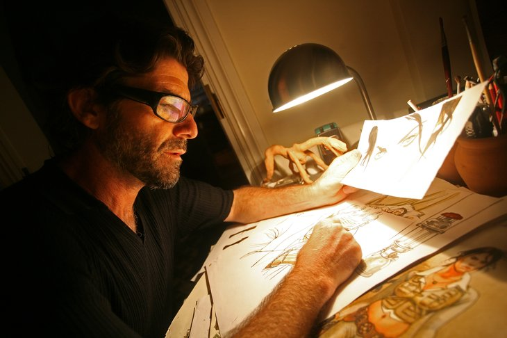 cartoonist in glasses drawing at his desk