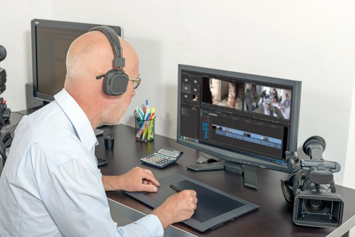 a senior edits video at a desktop computer