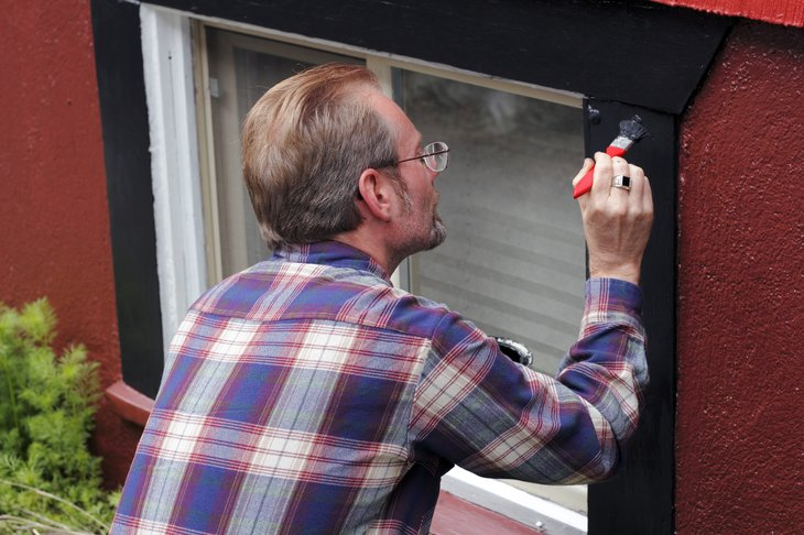 Man painting house trim
