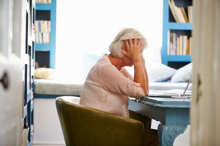 A stressed senior woman leans over her laptop computer and desk in a home office