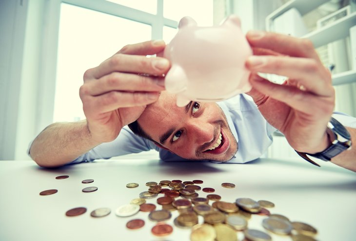 Man looking at piggy bank