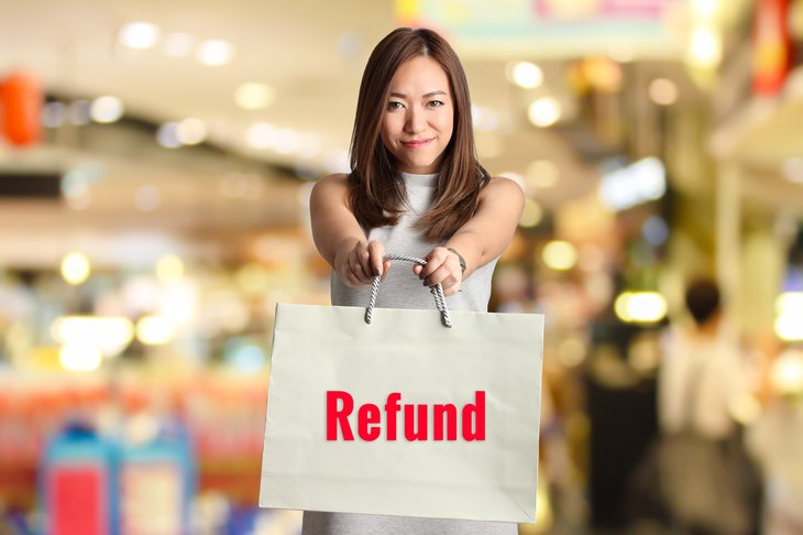 """Woman holding a bag labeled """"refund"""""""