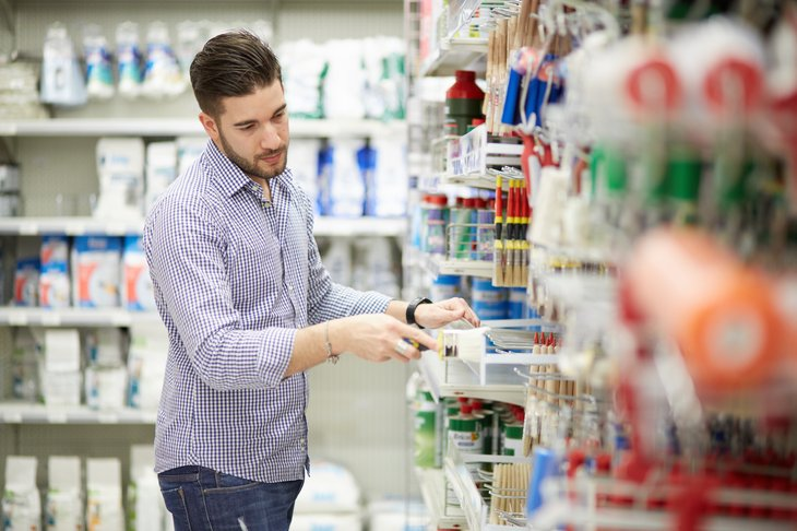 A man shops for painting supplies at a hardware store