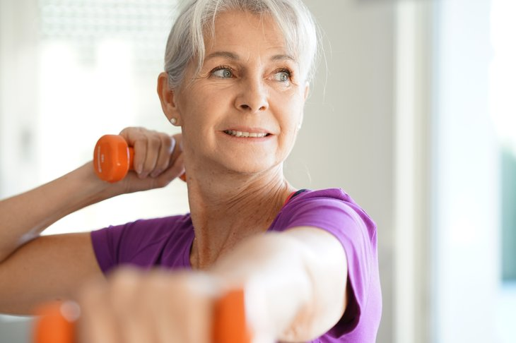A woman exercises with dumbbells