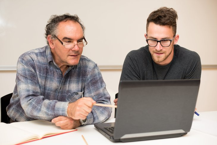 Professor and assistant working on a laptop