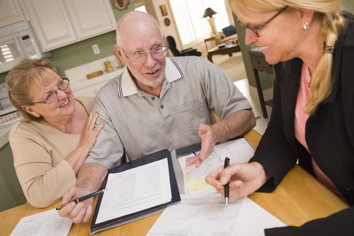 A senior couple goes over paperwork with a professional in their kitchen