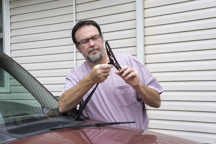 Man cleaning his car windshield wipers